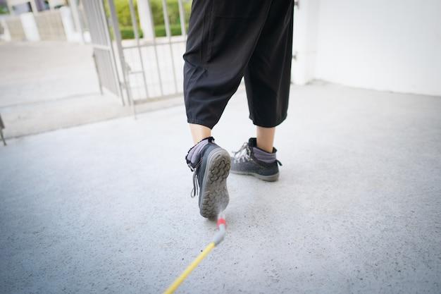 Lavoratore con spray detergente igienizzante chimico per disinfettare il patogeno del virus covid-19 sulle scarpe.
