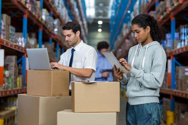 Lavoratore concentrato che scrive sul computer portatile e sulla compressa digitale