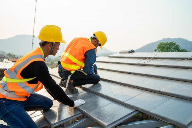 Lavoratore conciatetti in abiti da lavoro protettivi speciali e guanti che installano edificio residenziale in costruzione del nuovo tetto.