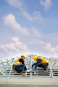 Lavoratore conciatetti nell'usura e nei guanti dell'uniforme protettiva, facendo uso della pistola sparachiodi pneumatica o pneumatica e installando le mattonelle di tetto concrete sopra il nuovo tetto, concetto di edificio residenziale in costruzione.
