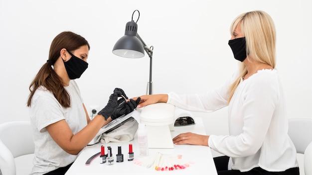 Lavoratore del chiodo di bellezza vista laterale che indossa guanti e maschera per il viso