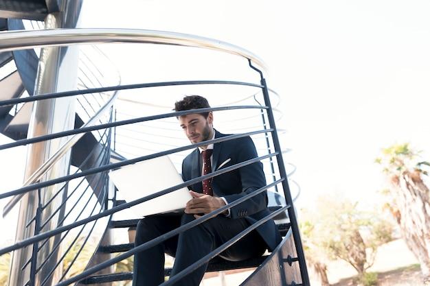 Lavoratore del colpo medio che si siede sulle scale