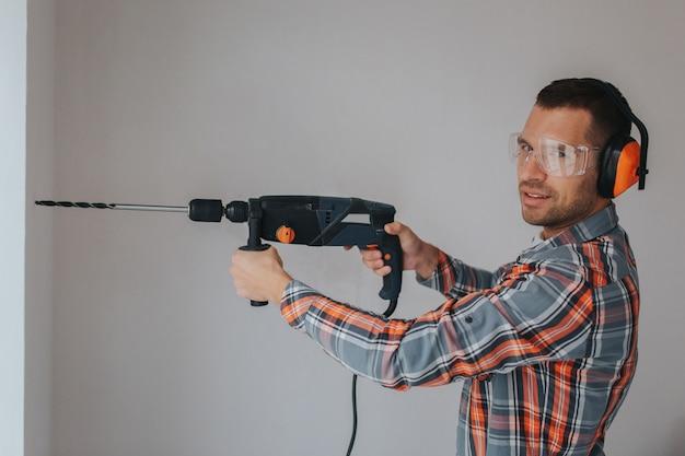 Lavoratore del costruttore con attrezzatura che fa foro in parete al cantiere