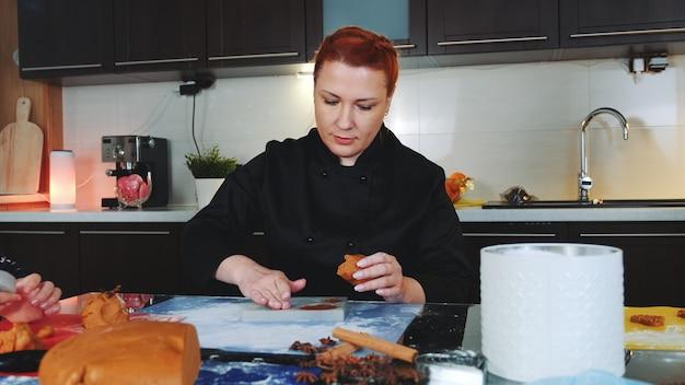 Lavoratore del forno che produce i biscotti del pan di zenzero riempiendo la teglia con la pasta di pasticceria.