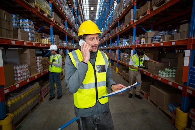 Lavoratore del magazzino che parla sul telefono cellulare e che tiene lavagna per appunti