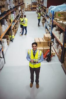 Lavoratore del magazzino che utilizza l'analizzatore della mano nel magazzino