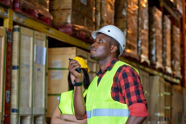 Lavoratore del magazzino che utilizza radioricevitore tenuto in mano per la comunicazione in un grande magazzino.