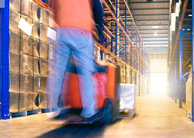 Lavoratore del magazzino con il carrello elevatore elettrico che funziona nella fabbrica del magazzino.