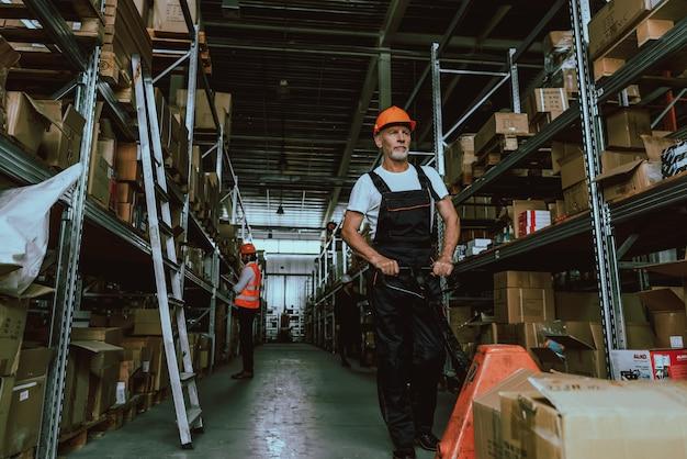 Lavoratore del magazzino in elmetto protettivo che per mezzo del carrello del carrello elevatore