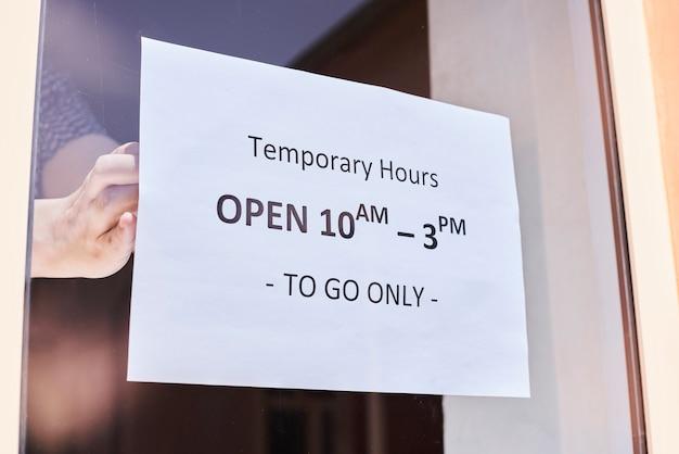 Lavoratore del negozio o del ristorante che appende un segnale di pericolo