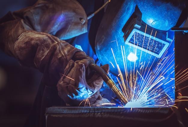 Lavoratore dell'industria alla fabbrica che salda struttura d'acciaio