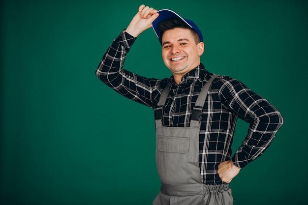Lavoratore dell'uomo in cappello isolato sulla parete verde