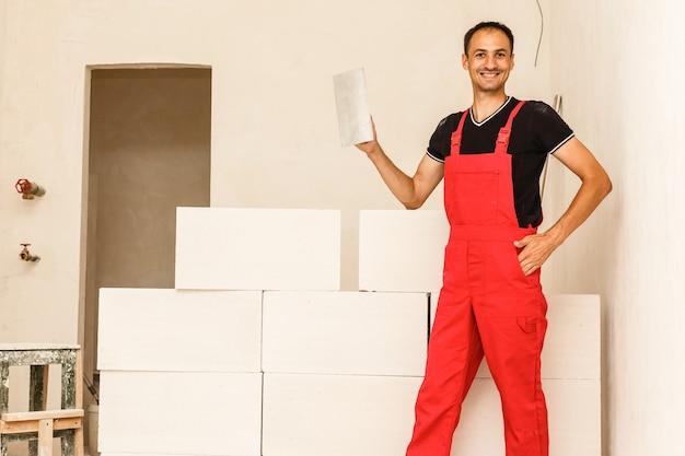 Lavoratore della muratura che fa un muro di cemento con il blocco e l'intonaco del cemento