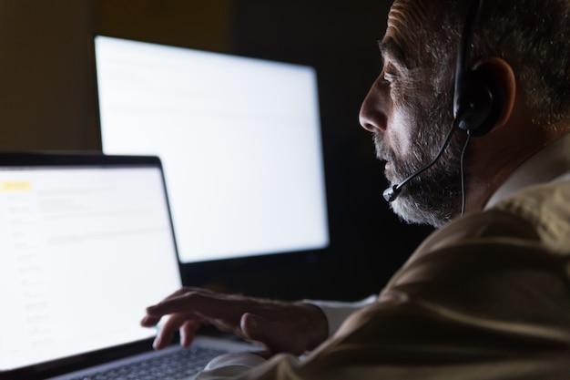 Lavoratore di call center in cuffia utilizzando il computer portatile