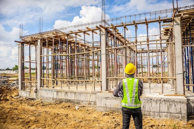 Lavoratore di ingegnere edile uomo d'affari asiatico in casco protettivo e carta cianografie a portata di mano al cantiere di casa