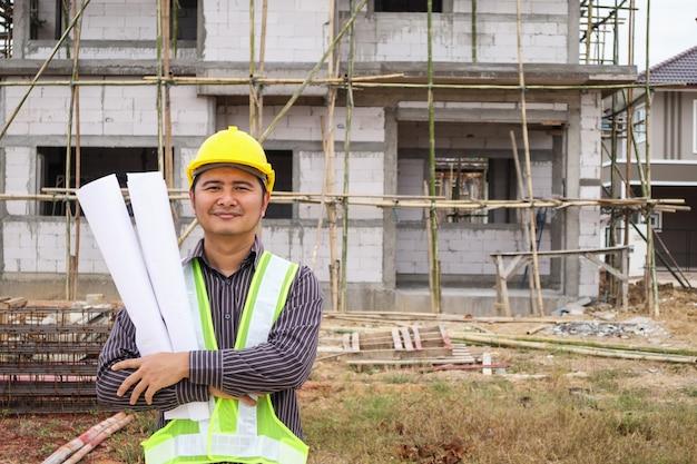 Lavoratore di ingegnere edile uomo d'affari asiatico in casco protettivo e carta cianografie a portata di mano in cantiere