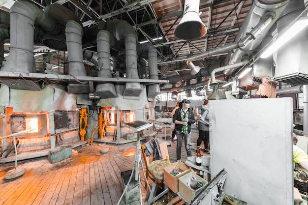 Lavoratore di produzione del vetro che lavora con l'attrezzatura di industria sulla fabbrica