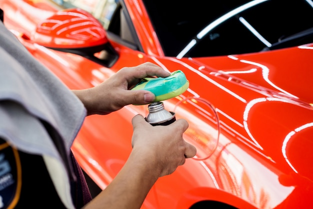 Lavoratore di servizio dell'automobile che applica rivestimento nano su un dettaglio dell'automobile