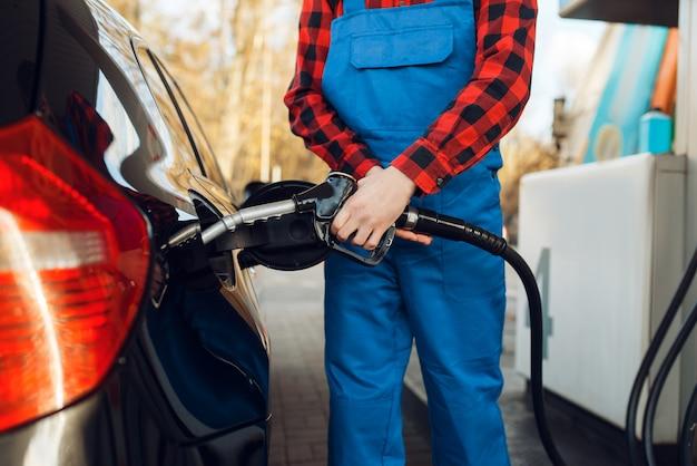Lavoratore di sesso maschile in automobile di combustibili uniformi sulla stazione di servizio