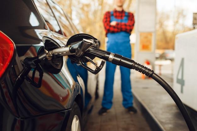 Lavoratore di sesso maschile in veicolo di combustibili uniformi sulla stazione di servizio