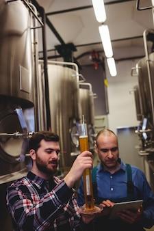 Lavoratore e proprietario che ispezionano birra alla fabbrica di birra