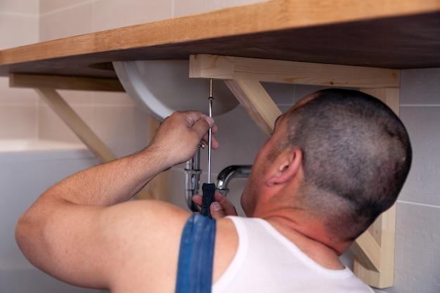Lavoratore idraulico maschio del primo piano in uniforme blu del denim, tuta, lavandino di riparazione in bagno con la parete delle mattonelle. servizio di riparazione professionale di impianti idraulici, installazione di tubi dell'acqua, scarico fognario montato sull'uomo