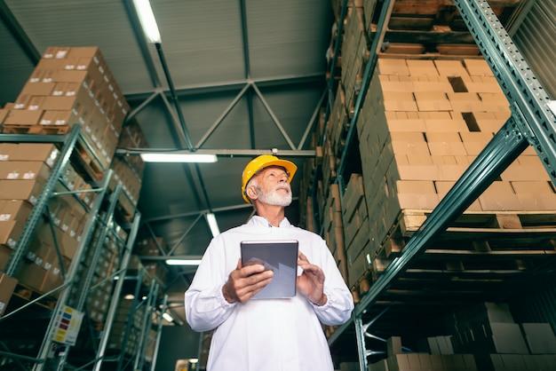 Lavoratore in magazzino tenendo la tavoletta.
