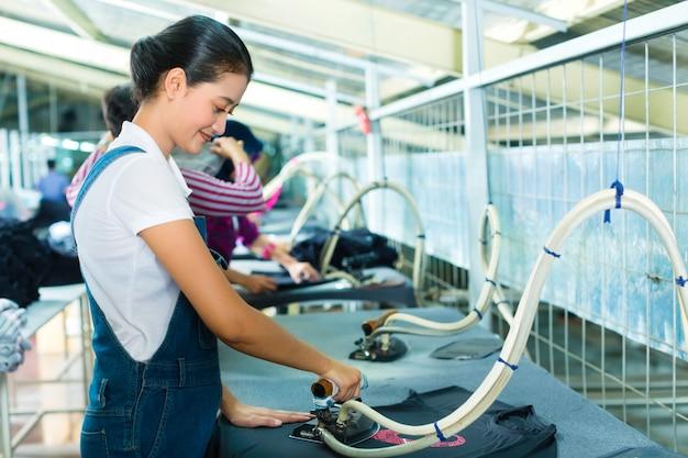 Lavoratore indonesiano con ferro piano nella fabbrica tessile