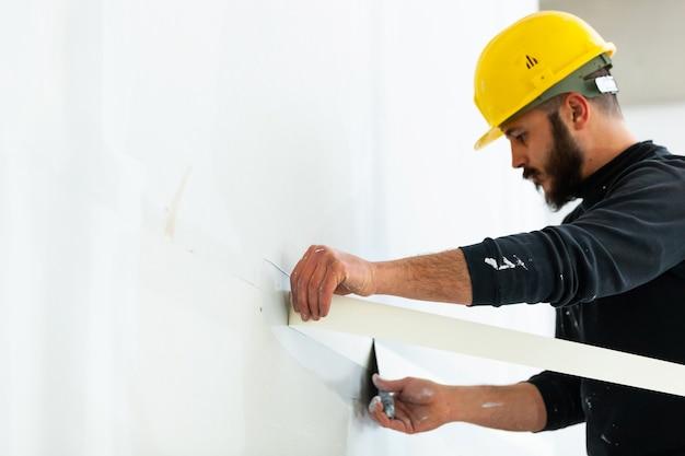 Lavoratore intonacare il muro di gesso.