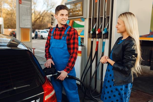 Lavoratore maschio in uniforme e donna alimenta il veicolo sulla stazione di servizio