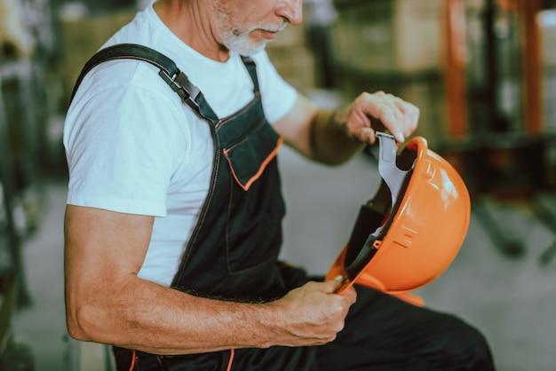 Lavoratore maturo del magazzino che tiene casco protettivo