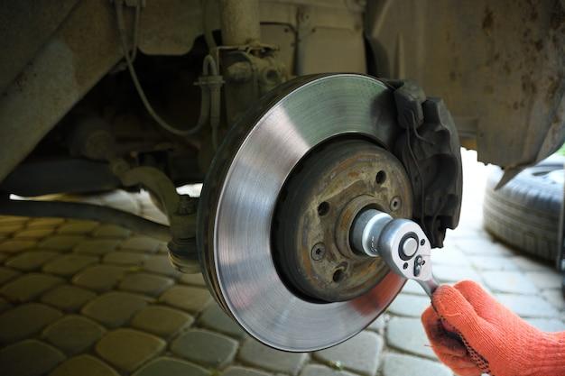 Lavoratore meccanico auto riparazione sospensione di automobile sollevata presso la stazione di officina garage auto riparazione