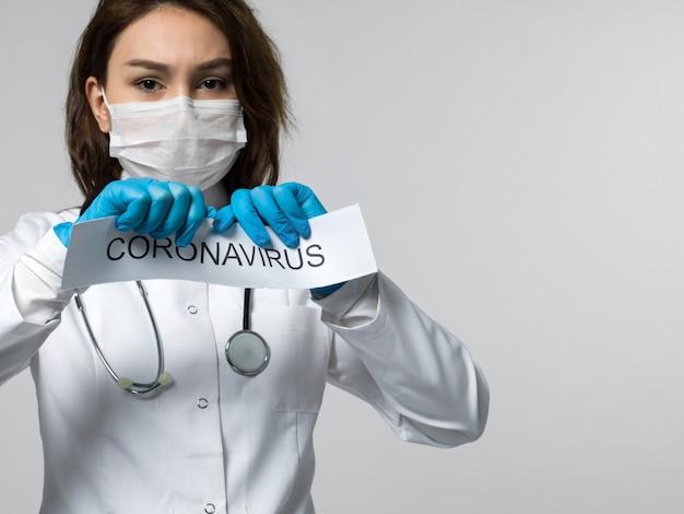 Lavoratore medico che fa a pezzi il pezzo di carta scritto coronavirus