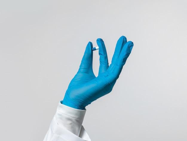 Lavoratore medico che tiene pillola blu in sua mano