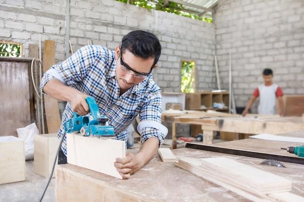 Lavoratore nell'area di lavoro del carpentiere tagliando la superficie dei mobili u