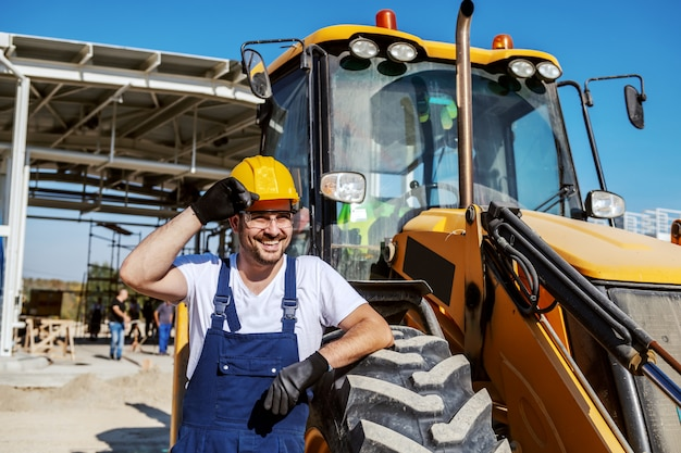 Lavoratore non rasato caucasico sorridente bello nel camion appoggiantesi generale e giudicare armi attraversate. giornata ordinaria in raffineria.