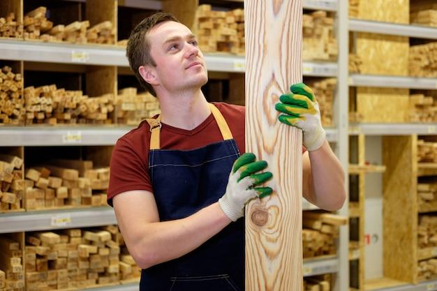 Lavoratore o venditore nella sezione di legno del deposito della costruzione o del magazzino sul lavoro