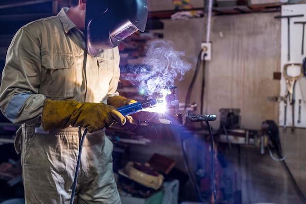 Lavoratore operaio industriale presso la fabbrica saldando la struttura d'acciaio con l'uniforme protettiva e la saldatura della maschera