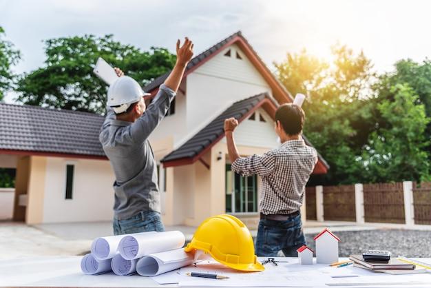 Lavoratore professionale dell'ingegnere di due uomini d'affari alla costruzione di casa.