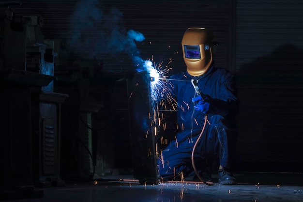 Lavoratore saldatore in acciaio usando la saldatrice elettrica