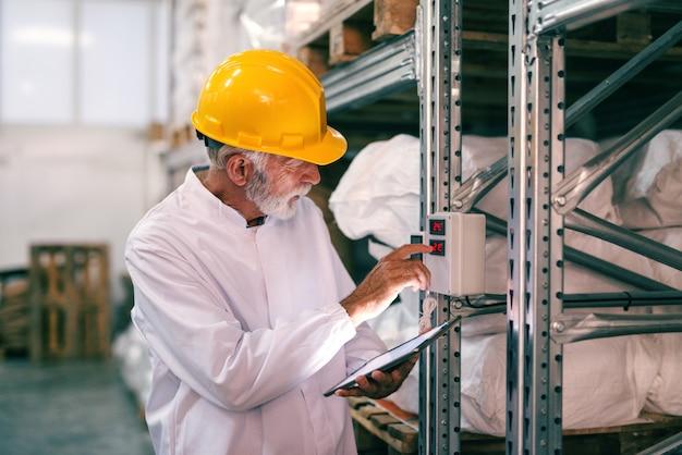 Lavoratore senior nell'usura del lavoro facendo uso della compressa e controllando temperatura nel magazzino.