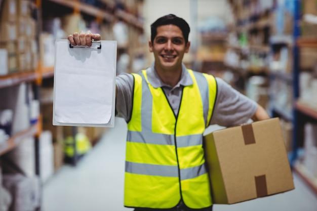 Lavoratore sorridente che mostra lavagna per appunti nel magazzino