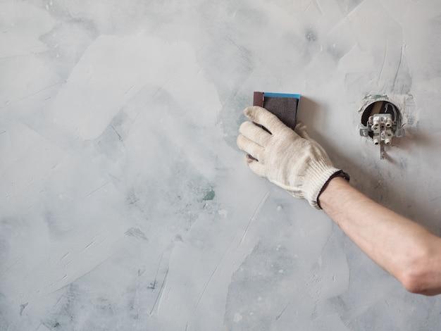 Lavoratore strofinare il muro con carta vetrata e preparare la superficie per la pittura. riparazione e ristrutturazione a casa. nuovo design degli interni.