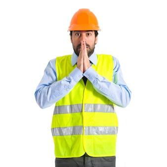 Lavoratore supplicando su sfondo bianco