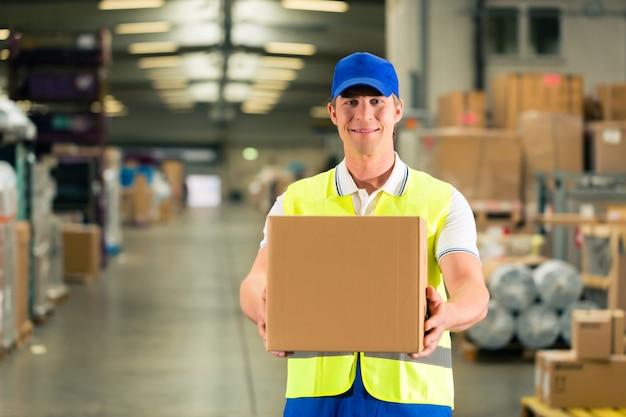 Lavoratore tiene il pacchetto nel magazzino di spedizione