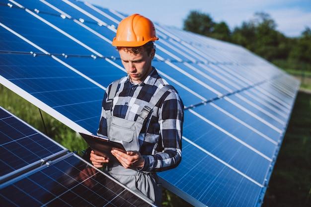 Lavoratore uomo nel firld dai pannelli solari