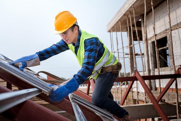 Lavoratori che installano tetti con indumenti di sicurezza costruzione di un tetto di una casa, di piastrelle di ceramica o di tegole cpac