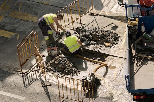 Lavoratori che riparano una tubatura dell'acqua rotta sulla strada