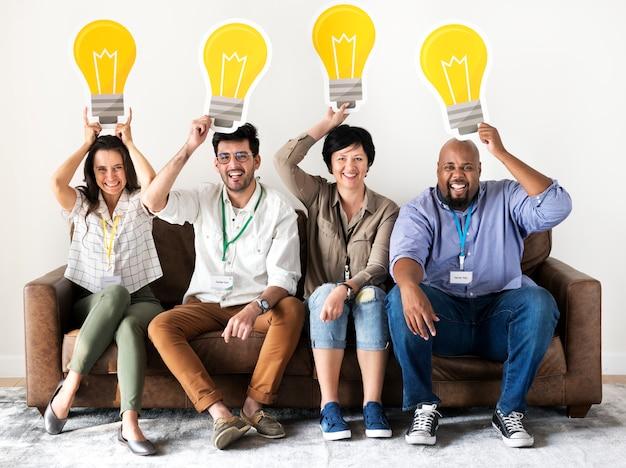 Lavoratori che si siedono e che tengono le icone della lampadina