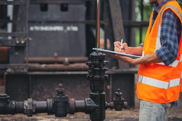Lavoratori che stanno e che controllano accanto alle pompe di olio funzionanti.